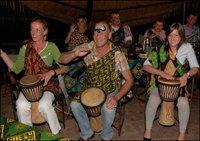 Guests beating drums at The Boma experience - Victoria Falls Safari Lodge