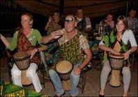 Guests beating drums at The Boma experience - Victoria Falls Safari Lodge