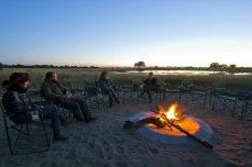 Warming up by the campfire at Camp Hwange, Hwange national Park, Zimbabwe