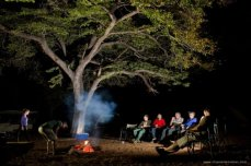Guests around a fire on an overnight camping safari in Chobe National Park, Botswana