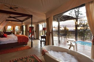 Luxurious suite at The Elephant Camp in Victoria Falls. Combine a safari in the Zambezi National park, plus return flights!