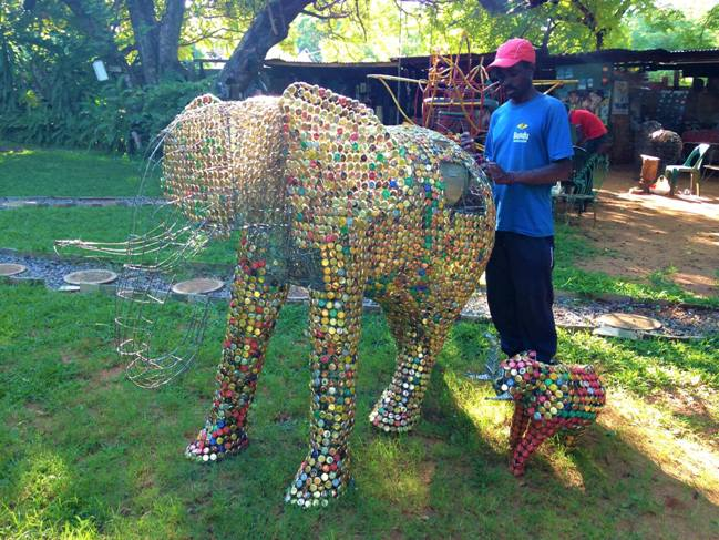 Artist in Victoria Falls constructing donation boxes from recycled material