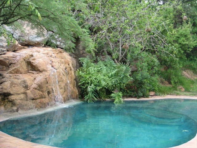Clear swimming pool with waterfall feature