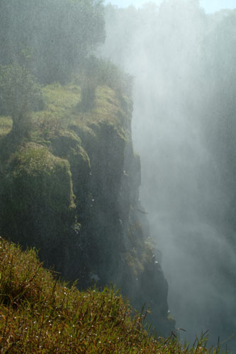 Thick spray of the Victoria Falls seen along a steep cliff in Zimbabwe