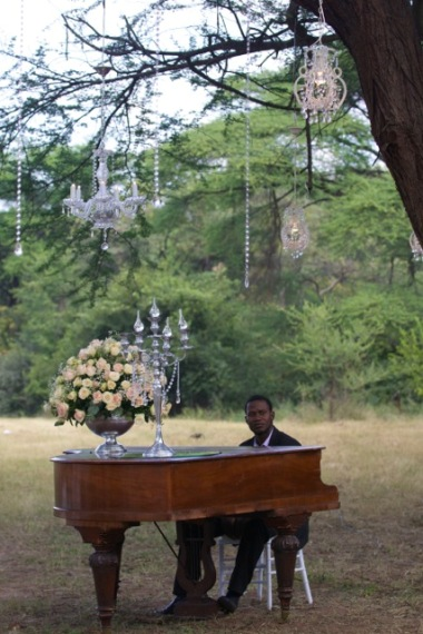 Piano man under a beautifully decorated tree in a Victoria Falls wedding